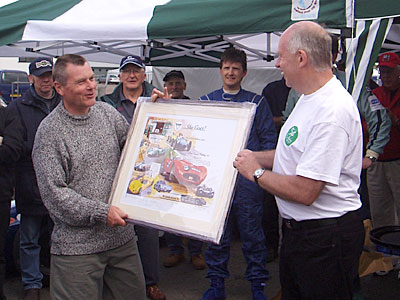 Roger Dunbar, wearing the special Mallory t-shirt while presenting F/J race winner Martin Walford with his prize, one of the multi-signed ELVA Prints.